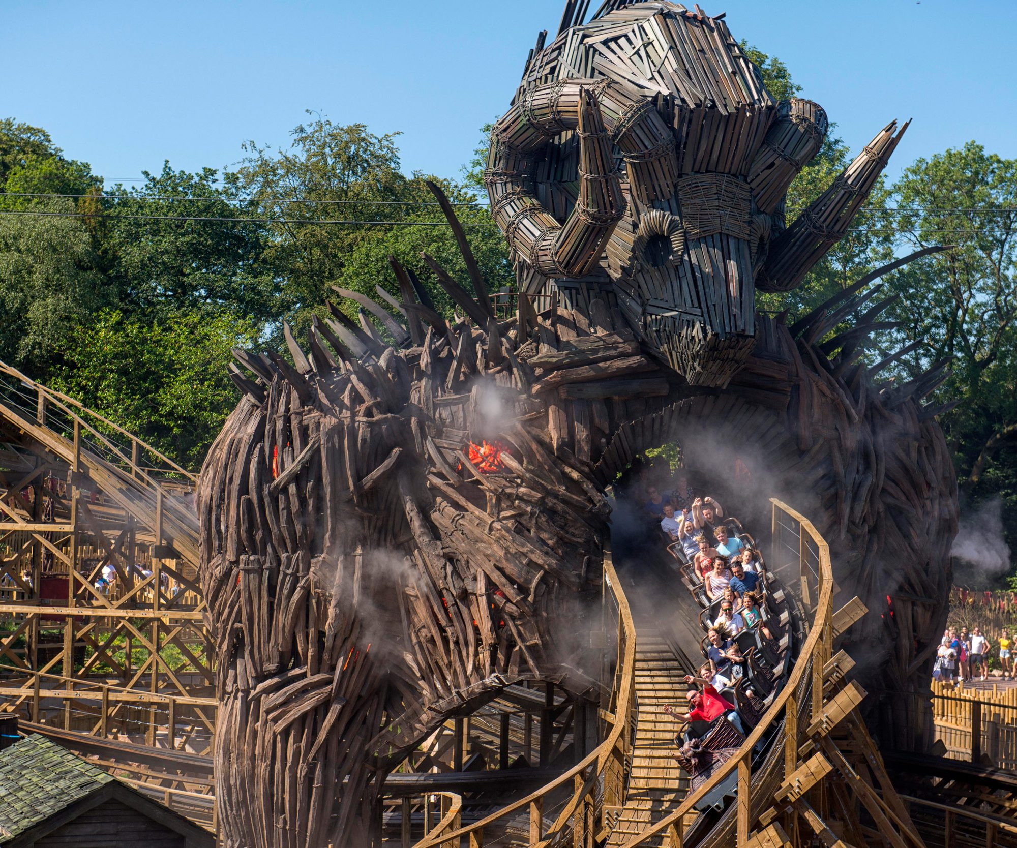 People scream as they ride on a wooden rollercoaster at a theme park.