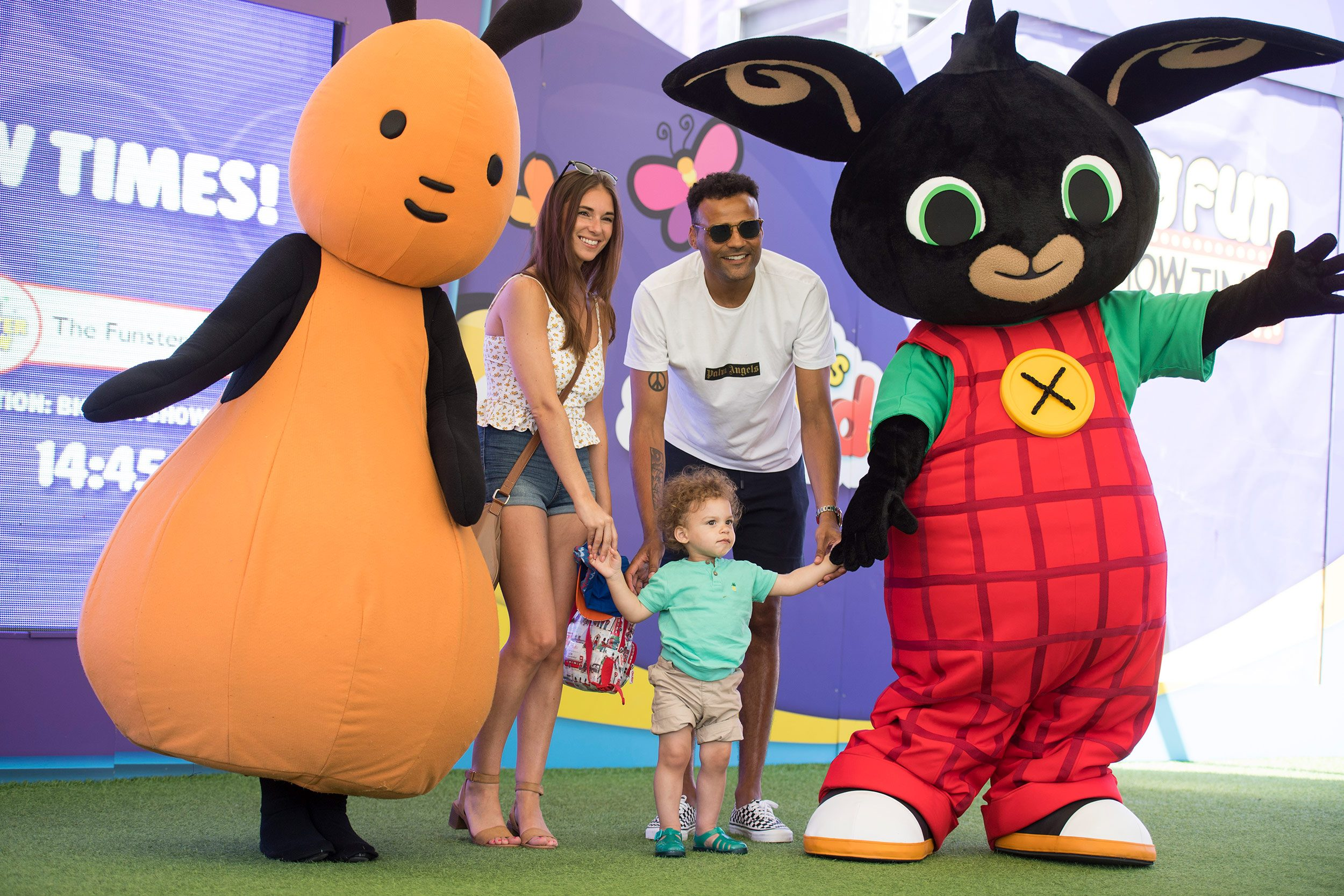 Parents take their child to meet two characters from the BBC's CBeebies at a theme park