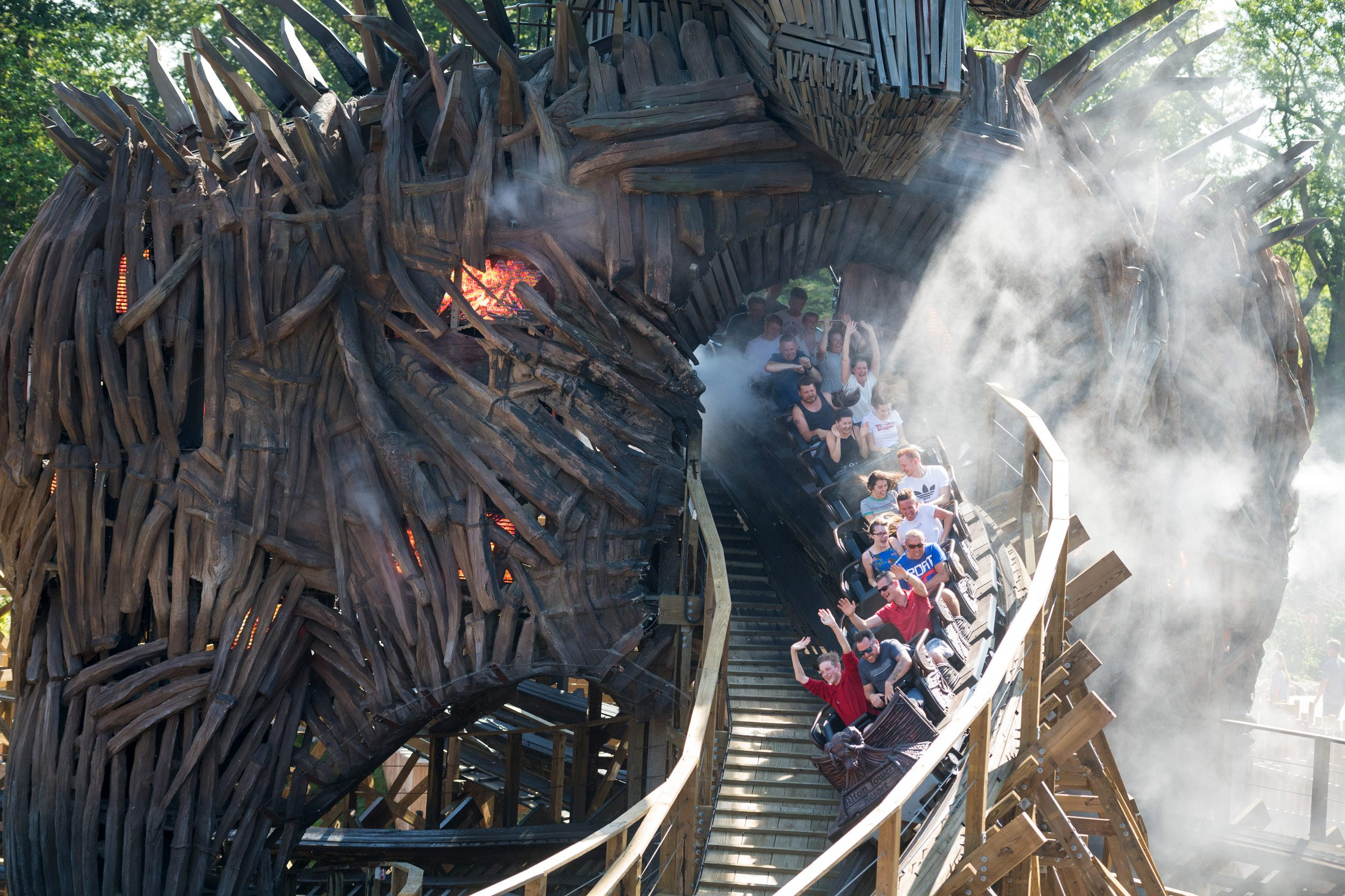 Riders on a rollercoaster exit a tunnel.
